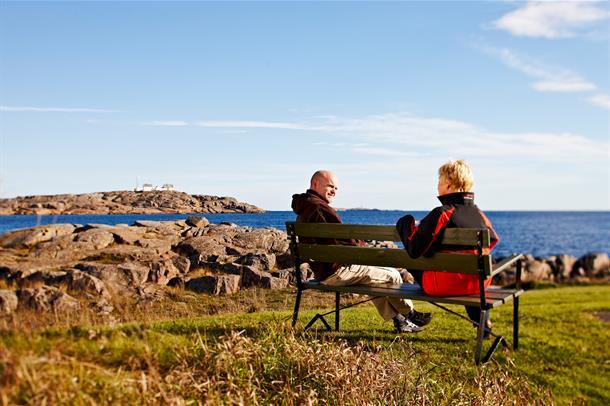 To personer som sitter på en benk ute ved havet