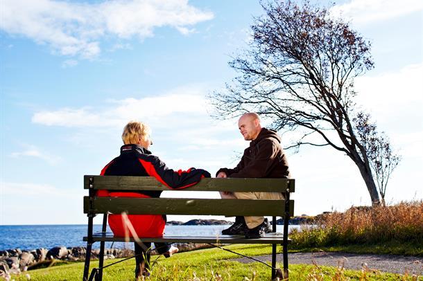 To som sitter på en benk ved vannet