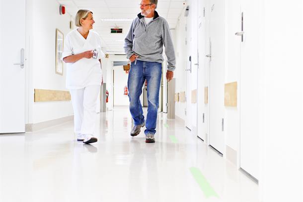 Pasient og behandler i korridor