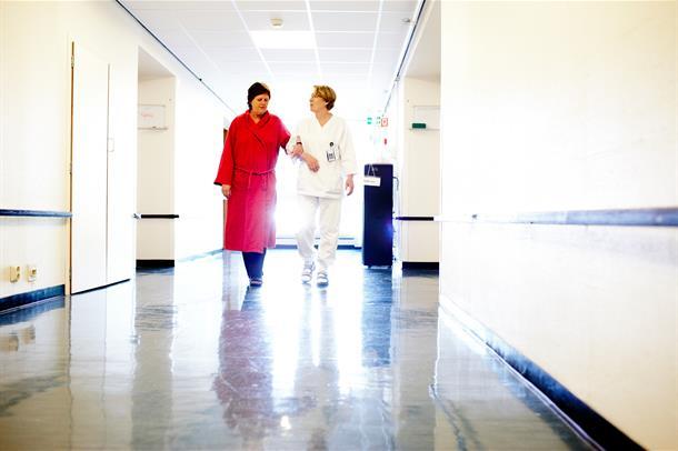 Dame i rød kåpe geleides av helsepersonell i sykehusgang