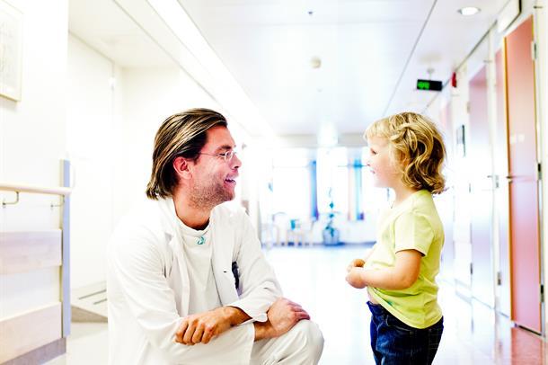 Bilde av ansatt og et barn som prater sammen