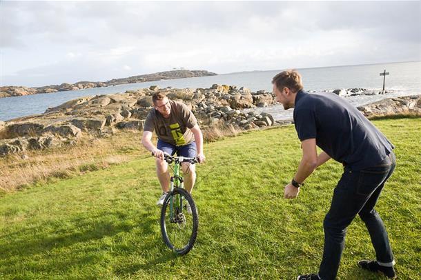 Bilde fra studien der Jarle Berge hjelper en pasient som sykler