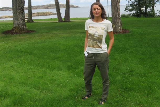 Kvinne med kystlandskap i bakgrunnen