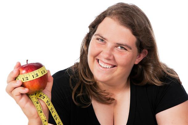 Kvinne med eple og målebånd